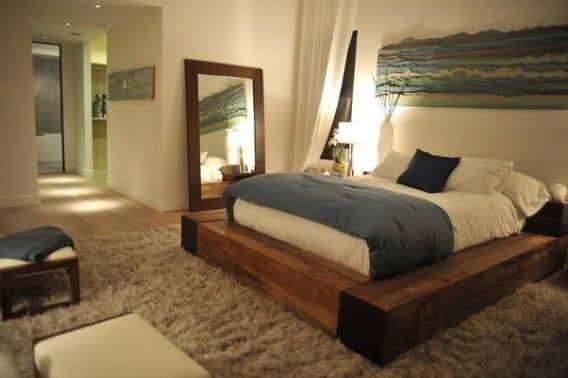 schlafzimer gemütlich einrichten mit diy bett aus massivholz, spiegel mit holzspiegelrahmen und wandeko über dem bett