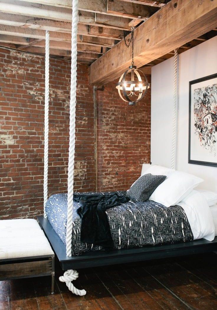 cooles schlafzimmer design im industrial style mit holzbalkendecke, ziegelwand und schaukelbett selbstgebaut aus holz