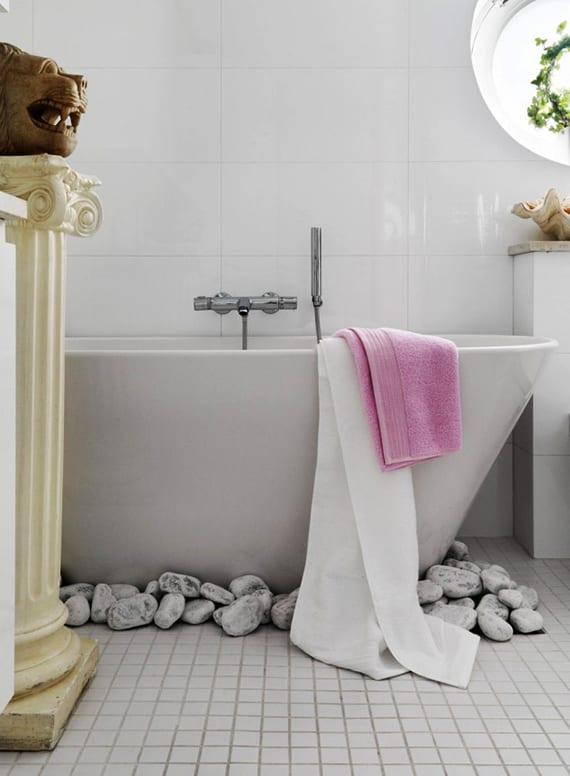 modernes badezimmer mit weißen mosaik-bodenfliesen, rundem fenster und freistehender badewanne weiß mit weißen steinen als dekoration