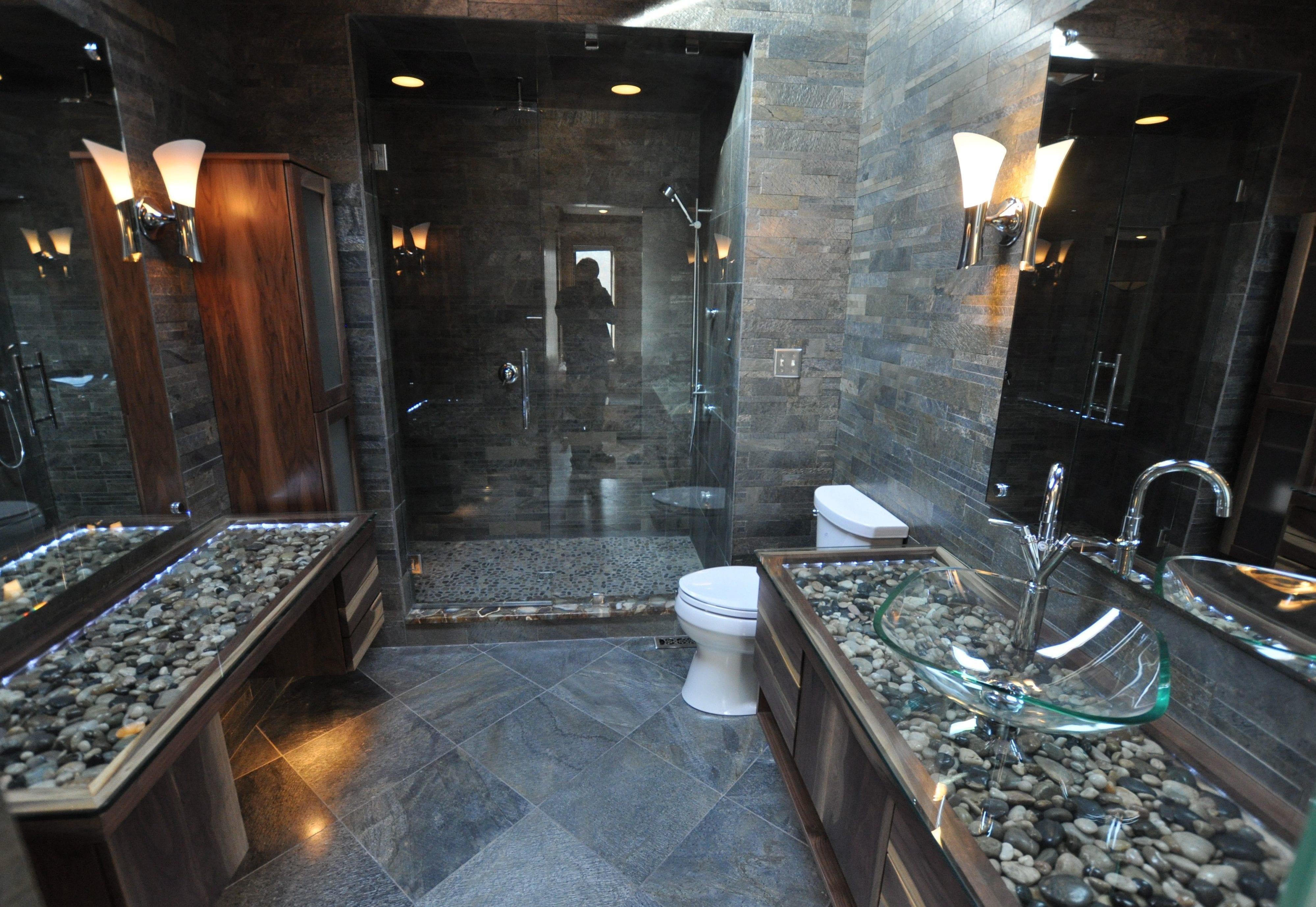 modernes badezimmer grau mit wandverkleidung aus naturstein und waschtisch aus holz mit steinen und waschbecken aus glas