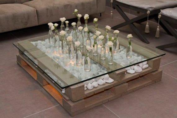 diy couchtisch aus paletten mit indirekter beleuchtung, weißen steinen und glasplatte