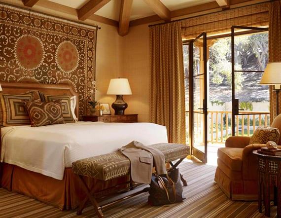 coole schlafzimmergestaltung im afrika style mit wandfarbe ocker, wandteppich hinter dem bettkopfteil aus leder, sitzbank holz und streifen-teppich