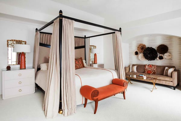 wohnidee für schlafzimmer weiß mit orangen Tischlampen auf weißen kommoden, himmelbett schwarz mit bettgardinen beige und wandnische mit sofa beige und coole wanddeko mit juju-hüten