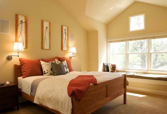 schlafzimmergestaltung mit wandfarbe gelb, holzbett mit orangen kissen dekoriert und zwei Schwinge-Wandleuchtern