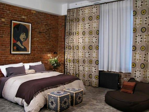 gemütliches schlafzimmergestaltung mit akzentwand aus roten ziegeln, gemusterten vorhängen in grün und grau, grauem teppich und sitzlissen im marokkanischen stil