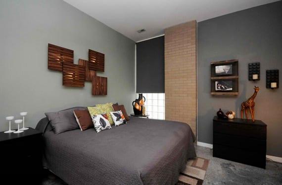 moderne schlafzimmergestaltung mit wandfarbe grau, ziegelwand, glasstein-fenster mit grauem fensterrollo und coole wanddeko mit schwarzen kerzenhalter und DIY wandleuchten aus holz