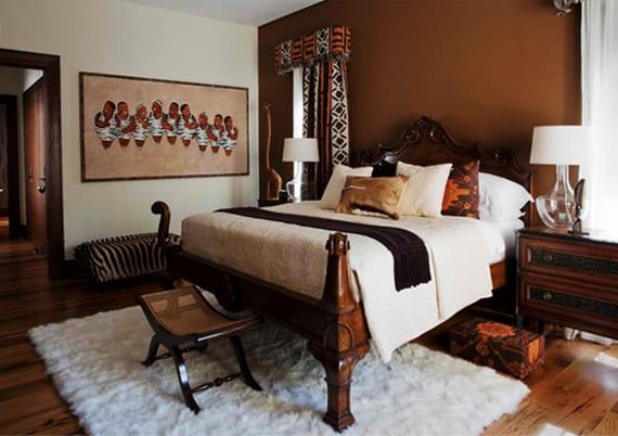 schlafzimmergestaltung im style afrika mit Akzentwand in Dunkelbraun, weißem teppich unter massivholzbett und zebra-ottomane