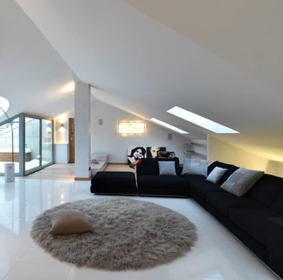 dachgeschosswohnung einrichten mit ecksofa schwarz und rundem teppich auf poliertem fußbodenbelag weiß
