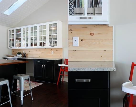 moderne küche mit kochinsel schwarz und küchenrückwand holz als akzent zu den weißen und schwarzen küchenschränken