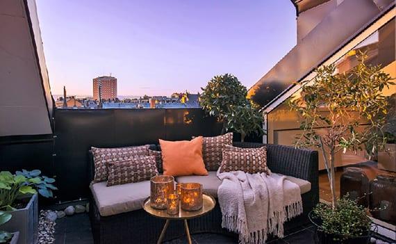 coole terrassengestaltung einer dachterrasse mit Rattansofa, kleinem kaffeetisch rund und steindeko