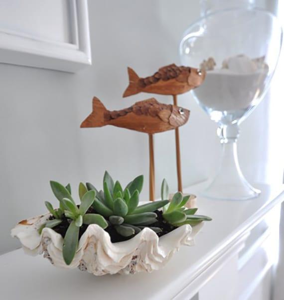 sideboard weiß dekorieren mit diy blumentopf für fettpflanzen aus muschel, fischfiguren aus holz und glasvase mit sand