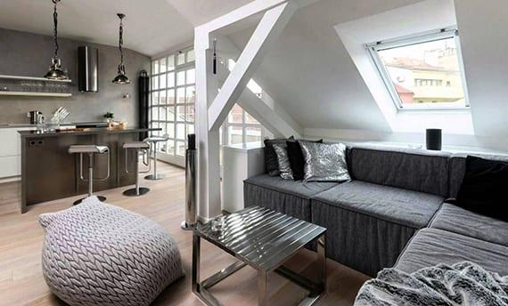 coole dachgeschosswohnung mit ecksofa grau unter dachschräge mit dachfenster und kleiner Küche mit Bar