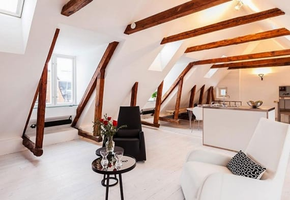 moderne dachgeschosswohnung mit gaubenfenstern und natürlich gelassenen deckenbalken und holzsparren_das moderne wohnzimmer in weiß mit kleiner kochinsel und essbereich