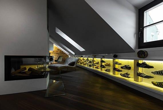 kreative raumgestaltung mit eingebauten vitrinen und indirekter wandbeleuchtung_moderne dachgeschosswohnung mit kamin, ziegelwand und dunklem parkett