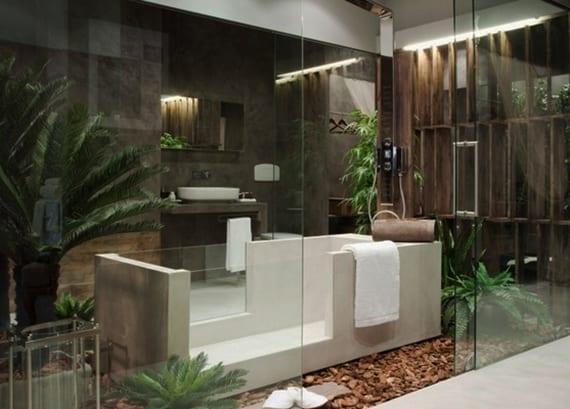 moderne badezimmergestaltung mit palmen, rechteckiger freistender badewanne mit glas und grauen wandfliesen aus naturstein