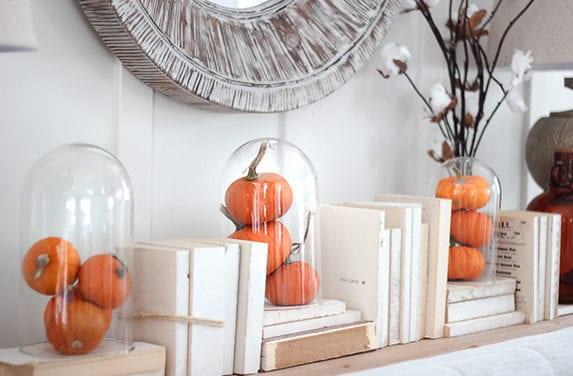 moderne dekoideen für sideboard dekorieren mit kleinen kürbissen in Glasglocken und weißen büchern