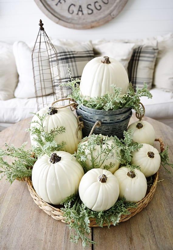 moderne tischdeko herbst mit weißen kürbissen und grünen pflanzen im weidenkorb