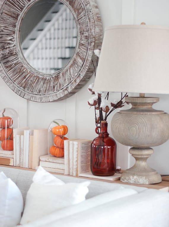 coole dekoiideen herbst in weiß und orange_sideboard dekorieren mit kürbissen unter Glasglocken, büchern und baumwollezweigen im roten glas