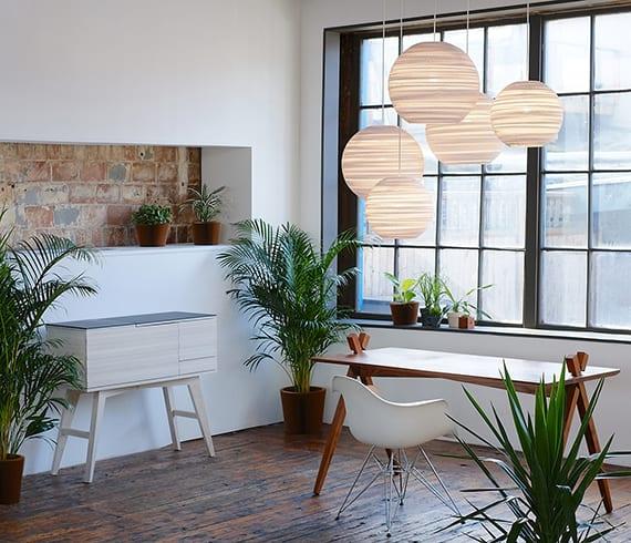 wohnideen für moderne zimmergestaltung mit eco friendly pendantlampen, schreibtisch und sideboard aus holz und viele pflanzen für grünen Akzent zu den weißen wänden
