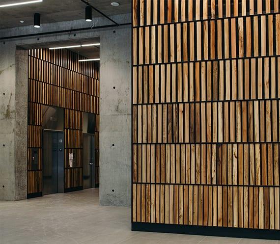 moderne gestaltungsidee mit wandverkleidung und Trennwand aus holzlatten in kombination mit betonwänden