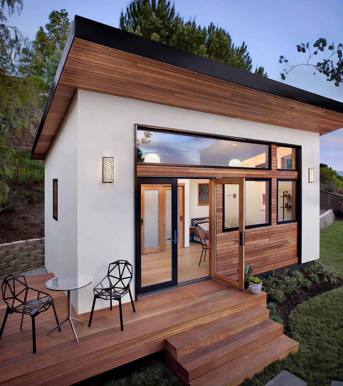 kleines fertighaus mit Holzterrasse in minimalistischem Stil mit Doppelglastür und bandverglasung in schwarz, Holzverkleidung und weißen Putzwänden