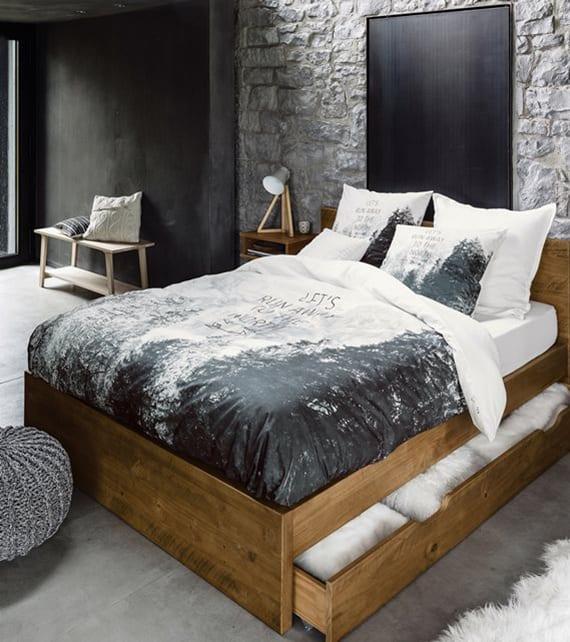 modernes schlafzimmer interieur mit maerwerk,wandfarbe schwarz, holzbettgestell mit schublade und baumwolle-bettwäsche mit schwarzweißem Berglandschaft-Printmuster