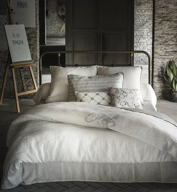 moderne bettwäsche aus reinem leinen in weiß mit mit hellgrauem Monogramm-Aufdruck und goldfarbener Paspel für rustikale schlafzimmergestaltung
