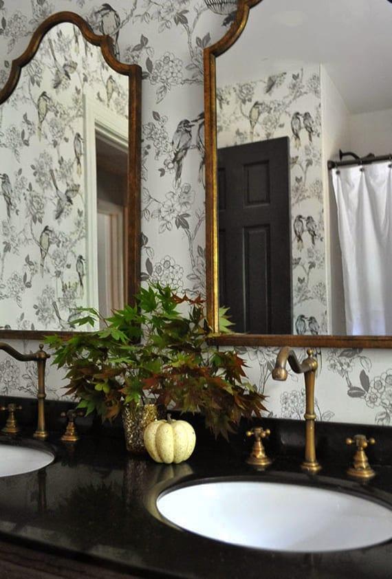modernes badezimmer mit schwarzem naturstein-waschtisch und tapete mit vogelmuster kreativ dekorieren mit kürbisdeko