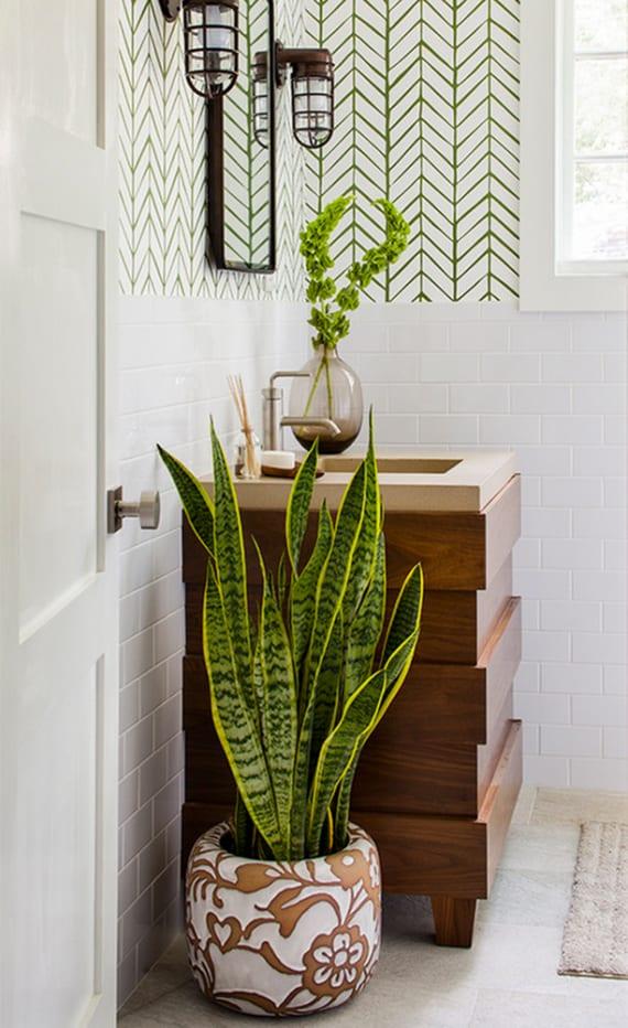 coole badezimmergestaltung mit tapete weiß und grün, modernem Waschtisch aus holz, kleinem wandspiegel mit vintage wandleuchtern und grünen pflanzen