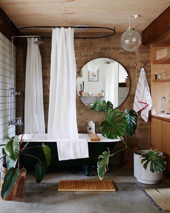modernes bad mit ziegelwand, schwarzer badewanne mit dusche und weiße duschvorhängen, waschtischschrank holz , spiegel rund und pflanzen