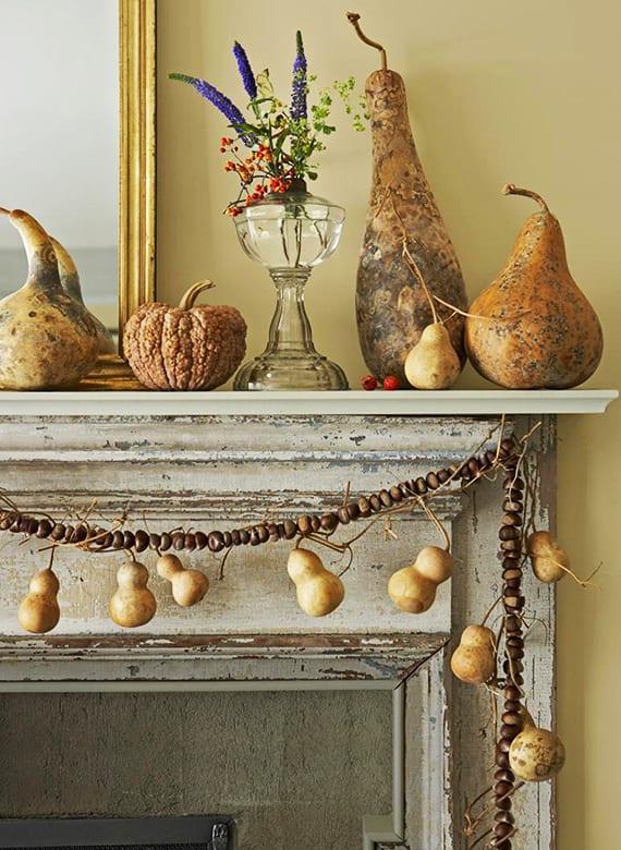 rustikale kamin-herbstdeko mit Spiegel in Goldrahmen, flaschenkürbissen und diy gerlande aus kastanien