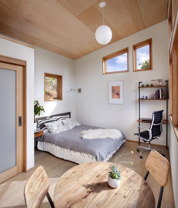modernes vorgefertigtes Haus mit gemütlichem schlafbereich und kleinem Homeoffice unter schrägdach