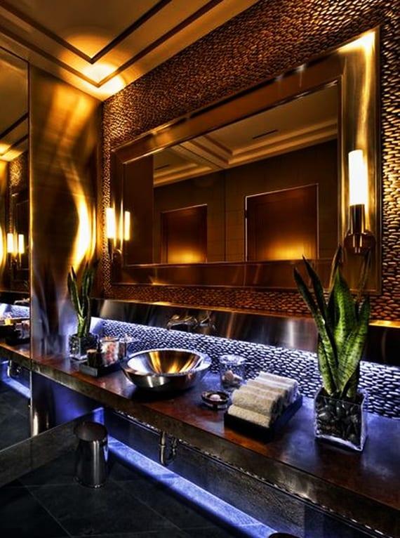 moderne badezimmergestaltung mit akzentwand aus schwarzen steinen, wandspiegel mit goldenem rahmen und wandleuchtern, waschtisch mit rundem waschbecken und pflanzen fürs bad