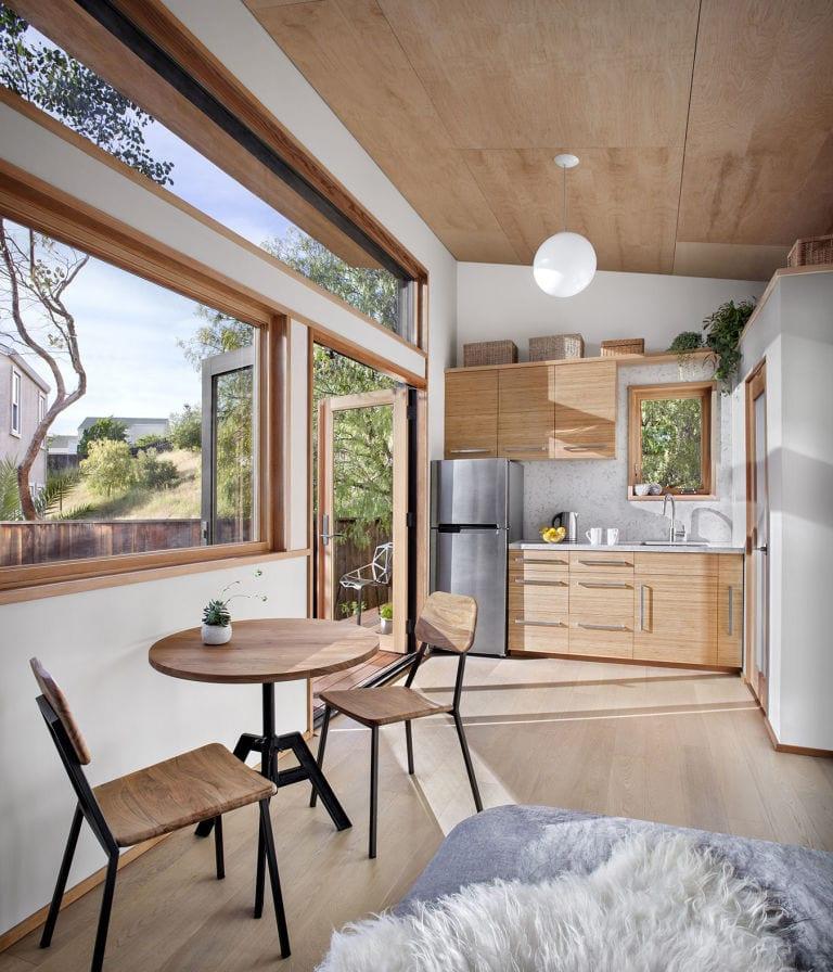 kleines traumhaus mit holzfußbodenbelag, holzdeckenverkleidung, kochnische mit rundholztisch im essbereich