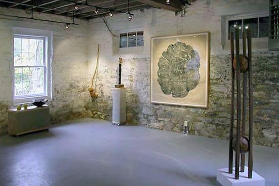 moderne raumgestaltung mit weiß gestrichenen Mauerwänden, baumstamm-Reliefdruck, betonbalkendecke mit lichtwerfern