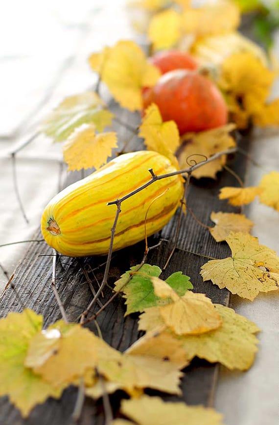 tisch eindecken mit Holzplatte, gelben weinblättern und orangen kürbissen