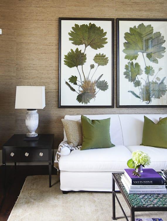 einrichtungsidee für modernes wohnzimmer mit tapete braun, sofa weiß, beistelltisch schwarz, couchtisch aus metall und coole wanddeko mit grünen blättern in bilderrahmen