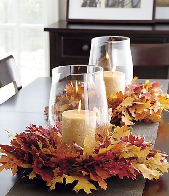 tisch herbstlich dekorieren mit kerzen in glasvasen und blätterkranz