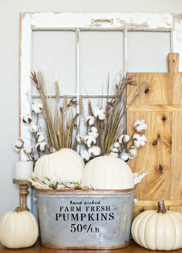 sideboard dekorieren mit holzfensterrahmen, holzschneidebrett und metalleimer mit weißen kürbissen und weizen