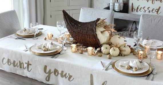 moderne tischdeko idee zu erntedankfest mit Füllhorn,weißen kürbissen und goldenen walnüssen_weiße servietten originell falten mit kleinen kürbissen