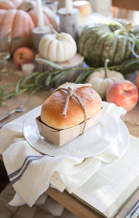 tisch eindecken zu thanksgiving mit selbstgebackenem Brott als Platzteller-Deko und mit Kürbissen und Kerzen auf Holzscheiben