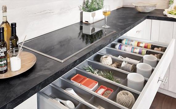 küchenideen für küchenrenovierung_küche modernisieren mit weißen küchenschränken, schwarzer arbeitsplatte in natursteinoptik, eingebauter Kochplatte und clevere schubladeneinrichtung