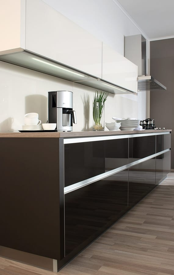 küchengestaltung mit wandfarbe grau, unterschränken in schwarz mit einbautürgriffen und weißen oberschränken mit einbauleuchten für beleuchtung der arbeitsplatte