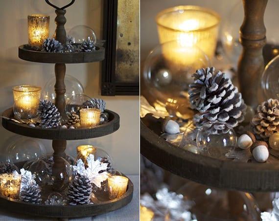 rustikale Weihnachtsdeko mit holzkuchenstand, weiß gefärbten zapfen und eicheln und glasteelichter