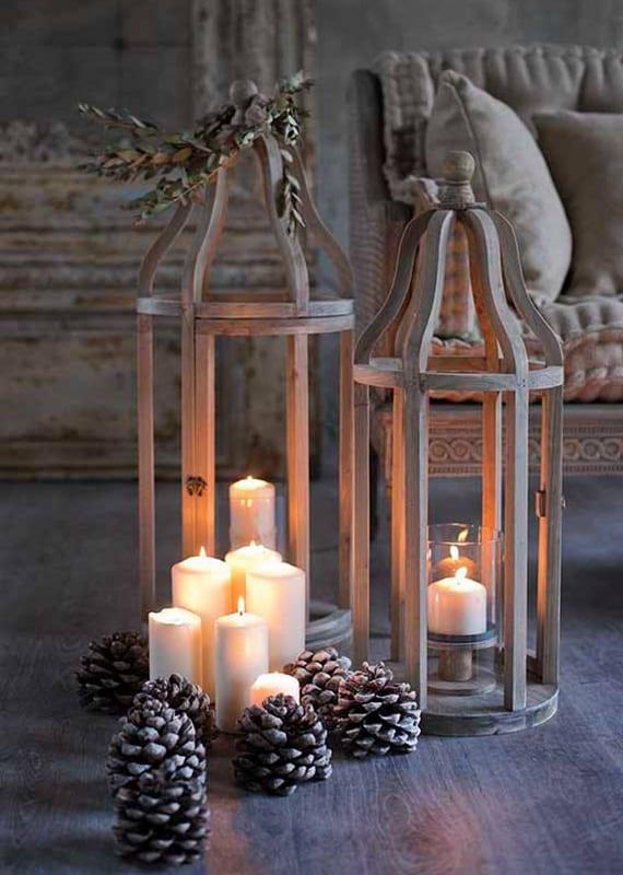 winterdekoration mit zapfen und weißen kerzen in großen Holzlaternen für romantische wohnzimmergestaltung im rustikalen stil