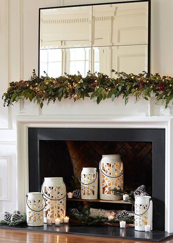 kamin modern und weihnachtlich dekorieren mit rechteckigem spiegel im schwarzen rahmen, weißen laternen rund und gerlande aus grünen blättern und lichterkette