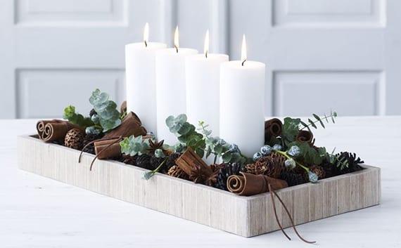 tisch weihnachtlich dekorieren mit weißen kerzen, zimtstangen,kleinen Zafpen und Grün in holztablett
