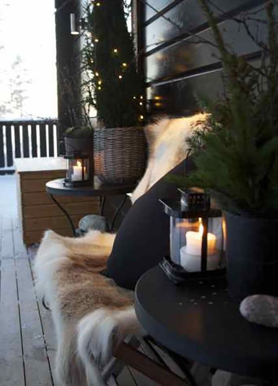 coole terassengestaltung im winter mit pelz, schwarzen kissen, laternen und tannengrün mit lichterkette