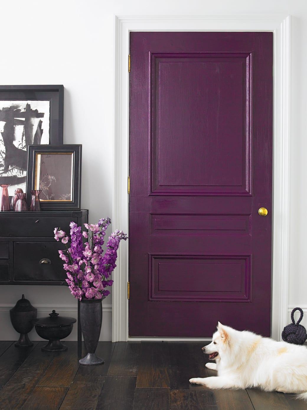 rustikale wohnraumgestaltung mit tür in lila farbe und vintage sideboard schwarz dekoriert mit schwarzen bilderrahmen und kleinen lilafarbigen glasvasen