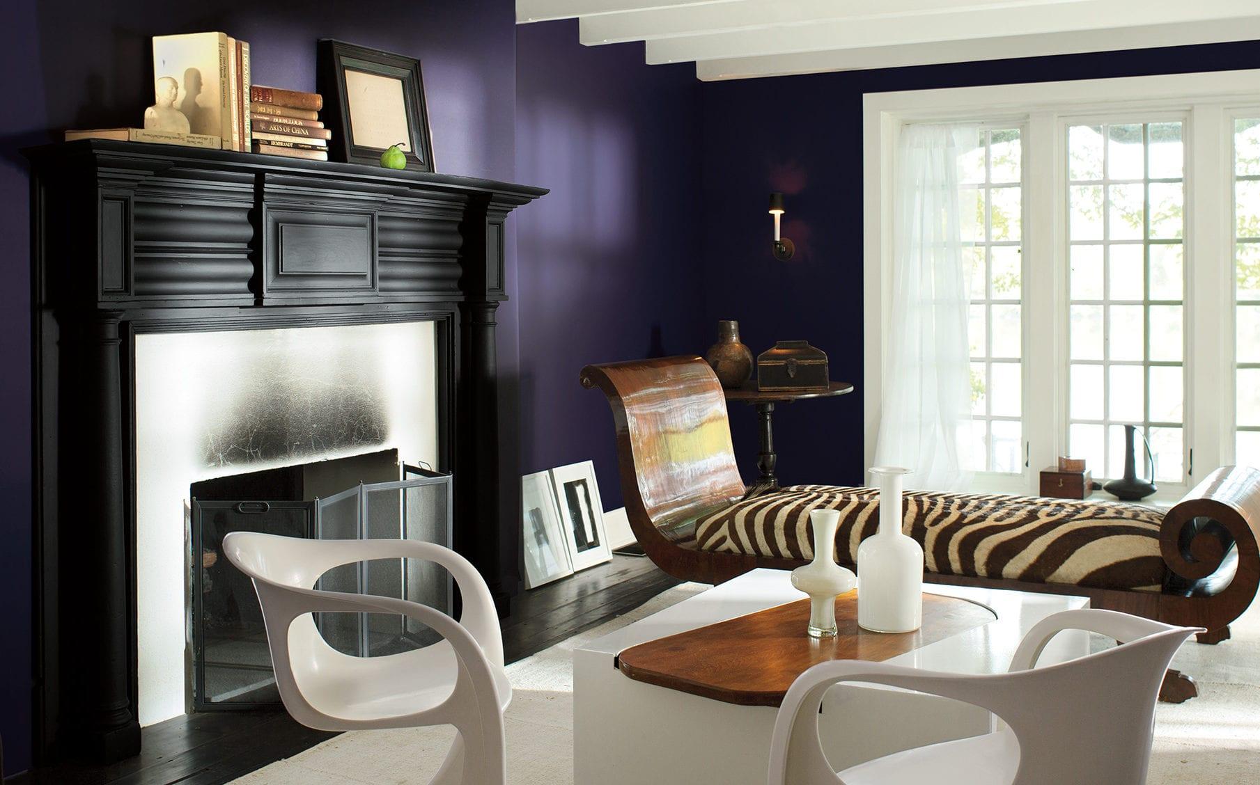 farbgestaltung wohnzimmer mit wandfarbe lila, modernes wohnzimmer mit kamin schwarz, weiße stühle und couchtisch und ottomane sofa aus holz mit zebramuster in weißbraun